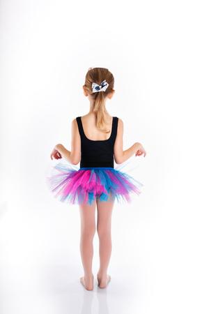 skirts: Funny little girl studying dance. Sport swimsuit.  Purple skirt. Little girl isolated on white background. Adorable little girl jumping in the air.