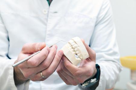Tandprothesen en materialen in de handen van een arts. tandarts kantoor