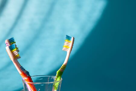 The dentist is checking the patients mouth. Colorful toothbrushes in glass. Closeup. Stock Photo