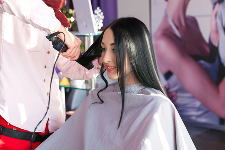 hairstylist: attractive hairstylist with a beautiful beaming smile cutting a womans hair in a professional hair salon