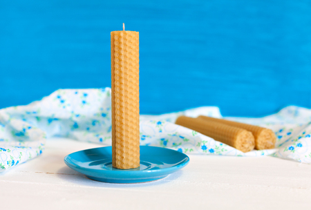 beeswax candle: Candle twisted from natural wax by hand on a blue plate. Against the background of the fabric and the other candles. Rustic Style. Gifts with their own hands