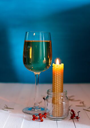 beeswax candle: Burning candle made of natural wax in a glass jar and a glass of white wine in the background. Jewellery and dried berries Stock Photo