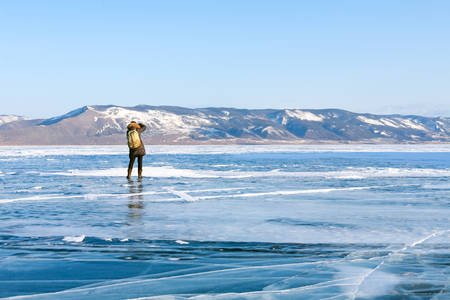 frozen lake: girl walking on the frozen lake Baikal