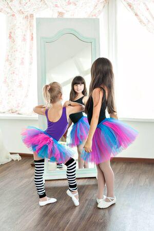 ragazze che ballano: two little girls dancing girls in fluffy skirts look in the mirror. dance Rehearsal
