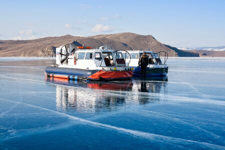 Hivus on ice. Two hovercraft. Ice on the surface of the transparent frozen Lake Baikal. Blue sky and clear ice. Horizon. Horizontal. Baikal in winter.