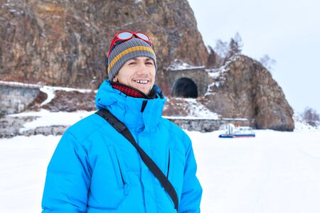 hovercraft: a man in a blue jacket in winter at Lake Baikal. Tunnels on the Circum-Baikal Railway. Tour of the winter Baikal on Hivus. Transport hovercraft. Stock Photo