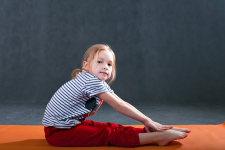 little girl doing gymnastic exercises for stretching on a yoga mat. Yoga for children. Stretching during training children's fitness.