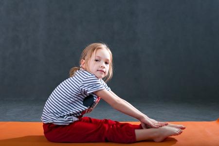 meisje dat gymnastiek- oefeningen doet voor het strekken op een yogamat. Yoga voor kinderen. Stretching tijdens de training fitness voor kinderen.