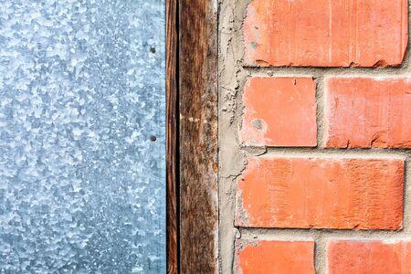 La combinazione dei quattro elementi di materiali da costruzione, struttura di legno duro, mattoni, cemento, lamiera mescolati insieme sul muro di una casa di campagna. Tecnologia strati e materiali compositi.