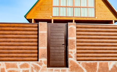 barrel tile: The fence of the new logs on a stone foundation and the front metal door. Wooden don the fence against the sky. Natural building materials