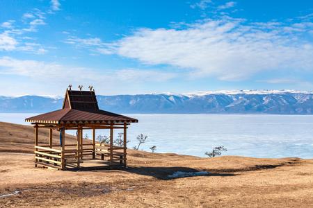Traditionele houten tuinhuisje in de Buryat-stijl aan de oever van het Baikalmeer in de winterbergen op de achtergrond. Winterlandschap op Olkhon-eiland. Regio Boerjat, Rusland, Siberië.