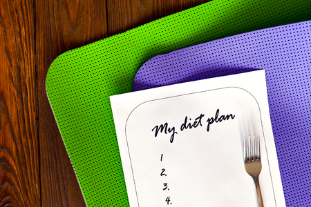 weight loss plan: Diet plan on a white sheet of paper. The new list and yoga mat green and purple on a wooden background. Weight loss and fitness. for dinner fork. The concept of love to a healthy lifestyle.
