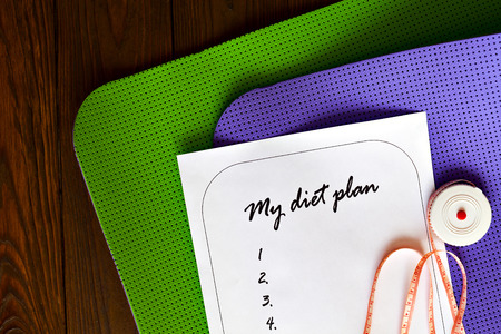 weight loss plan: Diet plan on a white sheet of paper. The new list and yoga mat green and purple on a wooden background. Weight loss and fitness. Measuring tape. The concept of love to a healthy lifestyle.