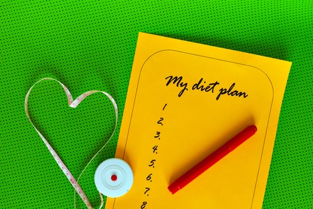 weight loss plan: List on a background of green Yoga mat. diet plan and an orange on a white sheet of paper. Measuring tape in the shape of a heart. The concept of love to a healthy lifestyle. Weight loss and fitness.