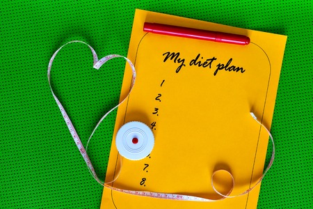 ethan: diet plan and an orange on a white sheet of paper. List on a background of green Yoga mat. Weight loss and fitness. Measuring tape in the shape of a heart. The concept of love to a healthy lifestyle.