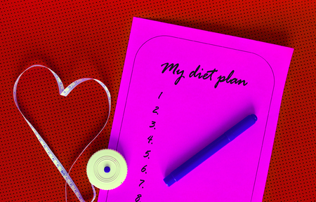 weight loss plan: Diet plan on a pink sheet of paper. List yogamat on a background of red. Measuring tape in the shape of a heart. The concept of love to a healthy lifestyle. Weight loss and fitness. Stock Photo