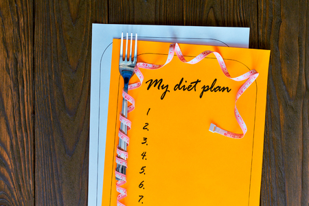 weight loss plan: Diet plan on orange and white sheet of paper with a measuring tape. The new list on a wooden background. An empty fork wrapped with a measuring tape. Weight loss and fitness.