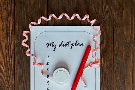weight loss plan: Diet plan on a white sheet of paper with a measuring tape. The new list on a wooden background. The concept of love to a healthy lifestyle. Weight loss and fitness.