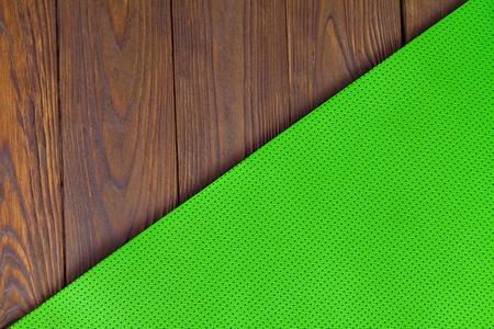 Detail des perforierten grünen Yoga-Matten auf dem hölzernen Hintergrund. Texture Yoga-Matten und Bretter. Boards braun. Die diagonale Ausrichtung. Das Konzept einer gesunden Lebensweise. Gewichtsverlust und Fitness. Standard-Bild