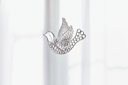 simbolo della pace: dove Souvenir di vetro, simbolo di pace e la primavera. Figurine di un uccello in volo Colomba trasparente. Un bel segno di primavera. Con lo spazio della copia. Giocattolo di vetro sullo sfondo di una finestra Archivio Fotografico