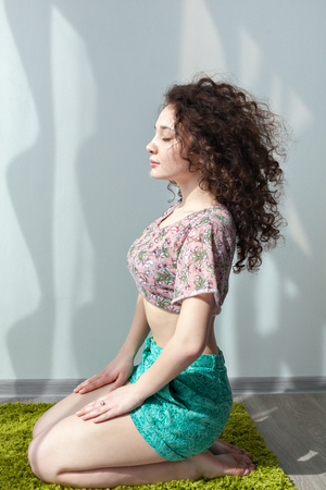 meditation room: Young girl with curly hair sitting on the floor, on a green rug, do stretching exercises. Meditation. Practice yoga at home. Enjoy life. Doing exercises in the morning in the bright sun room. Stock Photo