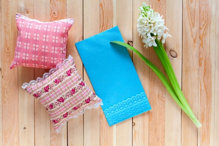 sachets: Small cotton pads with aromatic herbs and flowers. Delicate aroma sachets with lace on the wooden background. Light blue envelope with copy space. Gift for aromatherapy with a letter.