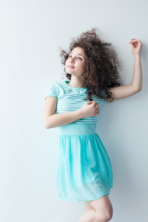 caucasian appearance: A young girl of Caucasian appearance dancing and dreams of a bright room on a summer day. Wavy curly hair and a blue dress. Rest and be happy. Stock Photo