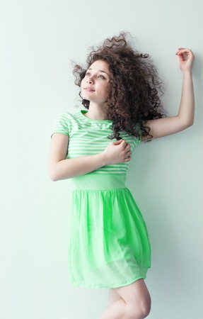 caucasian appearance: A young girl of Caucasian appearance dancing and dreams of a bright room on a summer day. Wavy curly hair and green dress. Rest and be happy.