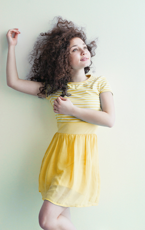 caucasian appearance: A young girl of Caucasian appearance dancing and dreams of a bright room on a summer day. Wavy curly hair and yellow dress. Rest and be happy.