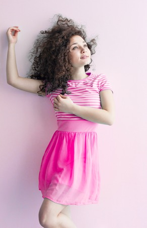 caucasian appearance: A young girl of Caucasian appearance dancing and dreams of a bright room on a summer day. Wavy curly hair and a pink dress. Rest and be happy.