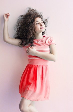 caucasian appearance: A young girl of Caucasian appearance dancing and dreams of a bright room on a summer day. Wavy curly hair and a red dress. Rest and be happy. Stock Photo