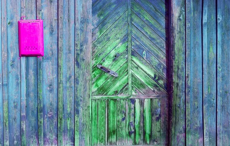 ornamentation: A fragment of an old wooden door and mailbox in a rustic style. Old blue peeling paint and red box pisem.Metallicheskaya handle, diagonal lines and ornamentation.