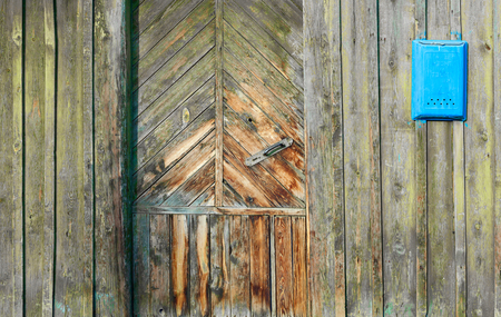 A fragment of an old wooden door and mailbox in a rustic style. Old peeling paint and box pisem.Metallicheskaya handle, diagonal lines and ornamentation.