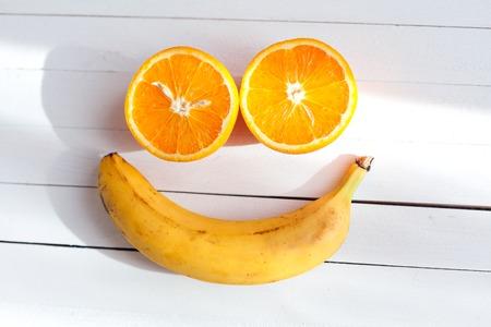 Lächeln Gesicht aus Früchten auf einem hölzernen Hintergrund. Obst Lächeln. Zwei Hälften von Orangen und eine Banane. Vitamine für eine gute Stimmung Standard-Bild - 55893365