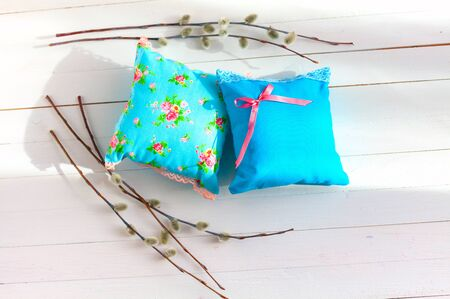 sachets: aromatherapy pillows, aromatization space using aromatherapy sachets. spa treatment. Small pillows Ornamental light blue color with lace. Handmade. White wooden background with willow twigs.