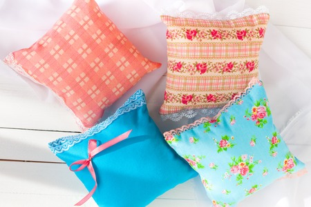 sachets: aromatherapy pillows, aromatization space. Four miniature decorative pillows pale blue and pink with lace. White wooden background. Home textiles. Handmade. for a good mood. Stock Photo