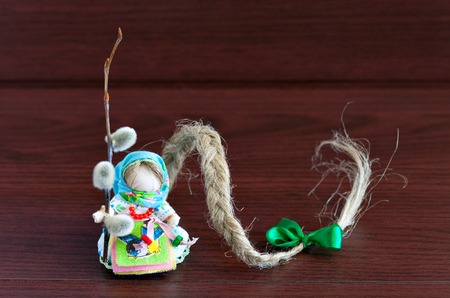 freckle: Russian folk doll. Handmade. Miniature doll cotton. Long hair is braided with a green bow. The symbol of spring. Doll Freckle, caddis fly on a brown wooden background.
