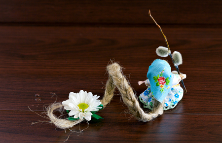freckle: Russian folk doll. Handmade. Miniature doll cotton. Long hair is braided with a green bow. The symbol of spring. Doll Freckle, caddis fly on a brown wooden background. Back view