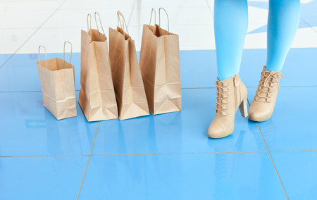 mischievous: Shopping at the mall.  Legs of a woman in a light blue tights and beige shoes near shopping bags. mischievous mood. Copy space. Legs and bags