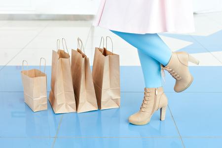Benen van een vrouw in een lichtblauwe legging en beige schoenen dichtbij het winkelen zakken. Winkelen in het winkelcentrum. Ruimte kopiëren. Benen en tassen. ondeugende stemming.