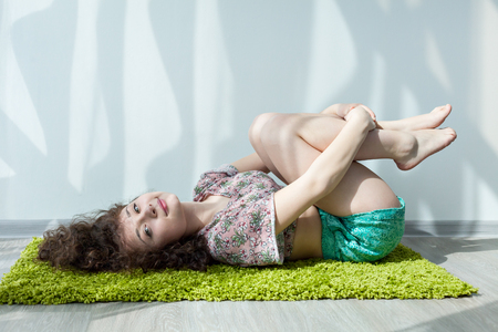 meditation room: Young girl with curly hair lying on the floor, on the green carpet, do stretching exercises. Exercising in the morning in the bright sun room. Meditation. Practice yoga at home. Enjoy your life.