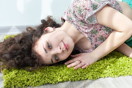 meditation room: Young girl with curly hair lying on the floor, on the green carpet, smiling and enjoying life. Tender feelings. Meditation. Practice yoga at home. Exercising in the morning in the bright sun room.