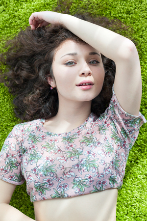 hugging knees: Young girl with curly hair lying on the floor on carpet, smiling and enjoying life. Tender feelings. Meditation. Practice yoga at home.