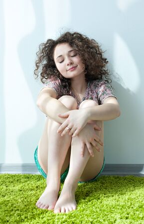 hugging knees: Young girl with curly hair, sitting on the floor hugging his knees on the green carpet, smiling and enjoying life. Tender feelings. Meditation. Practice yoga at home.