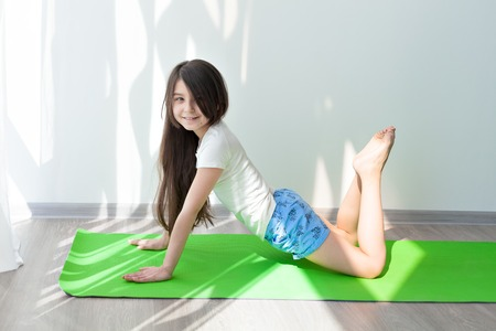 little girl doing gymnastics on a green yoga mat. childrens fitness and yoga for children. fitness exercises and stretching. Stock Photo