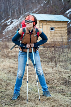 trekking pole: With a backpack on the background of the house in the mountains. Young woman with trekking pole outdoors.