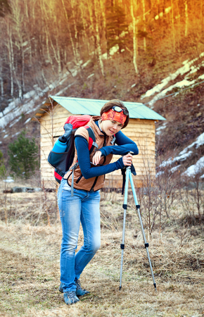 trekking pole: Young woman with trekking pole outdoors. With a backpack on the background of the house in the mountains.