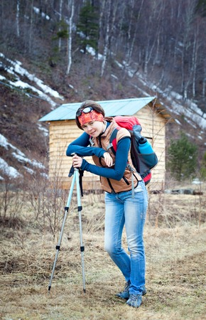 trekking pole: Young woman with trekking pole outdoors. With a backpack on the background of the house in the mountains. solo Climbing