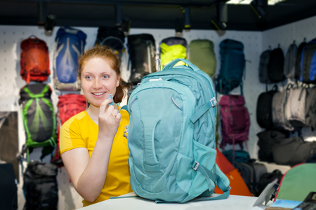 gamme de produit: Young Caucasian girl in yellow t-shirt buys Tourist backpack in the store. Specialized products for tourism and mountaineering. The buyer on the background of a display of tents and backpacks. Banque d'images