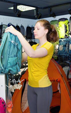 mochila de viaje: niña caucásica joven de la camisa amarilla está considerando mochila de viaje en la tienda. productos especializados para el turismo y el montañismo. El comprador en el fondo de una pantalla de carpas y mochilas Foto de archivo